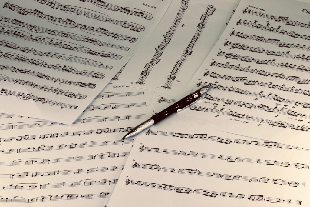 A pen sits on top of scattered pages of sheet music.